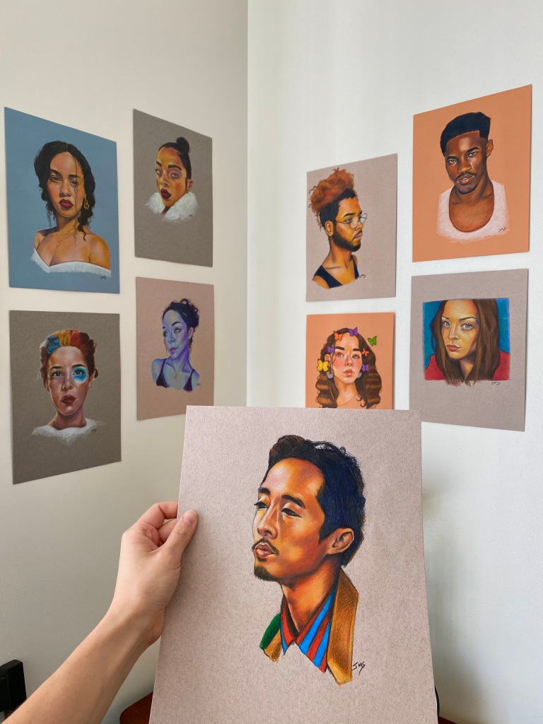 A photo of the author's colored pencil portrait drawings, hanging on the wall of her bedroom. She holds up a portrait of actor Steven Yeun in the foreground.